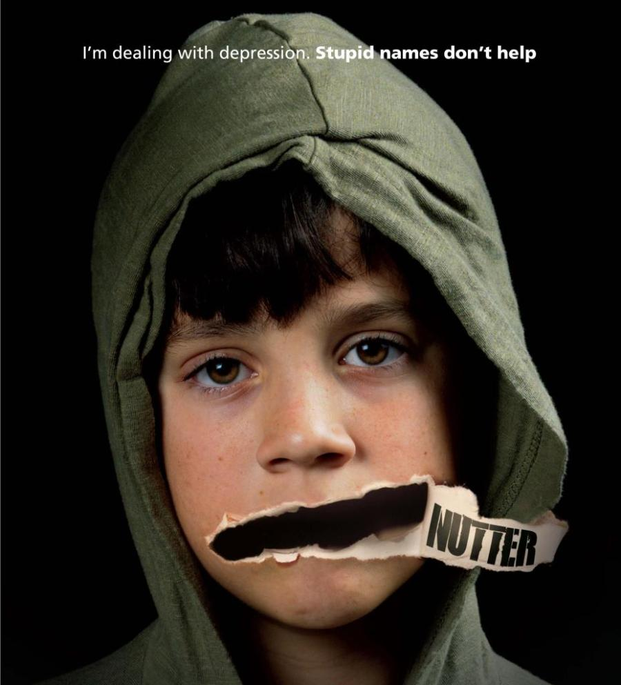 Boy with hoodie on and paper torn away from the mouth with the word 'Nutter' written on the underside. Text at top says 'I'm dealing with depression. Stupid names don't help'